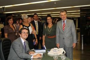O autor André Santos de Albuquerque autografando a obra para o Ministro do TCU, Valmir Campelo